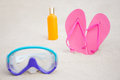 Close up of diving mask flip flops and suntan lotion bottle on pink sandy beach Royalty Free Stock Images