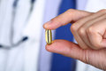 Close-up of doctor fingers holding fish oil capsule Royalty Free Stock Photo