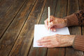 Close up of elderly male hands on wooden table writing on blank paper Royalty Free Stock Photography