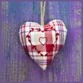 Close-up of embroidered heart shape on purple wooden surface. Royalty Free Stock Photo
