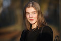 Close up emotional portrait of young happy beautiful woman with a slightly smile wearing black coat posing at evening golden hour Royalty Free Stock Photo