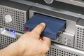 A close up of a it engineer technician insert a backup tape in a backup robot in a rack shot in a data center Royalty Free Stock Photos