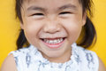 Close up face of asian kid toothy smiling facial face with happi happiness emotion on yellow wall use for children lovely emotion Stock Images