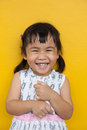 Close up face of asian kid toothy smiling facial face with happiness emotion on yellow wall use for children lovely emotion and de Royalty Free Stock Photo