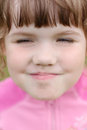 Close up of face little beautiful happy grimacing girl in pink Stock Photography