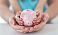 Photo : Close up of family hands with piggy bank blue on background