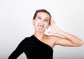 Close up fashion photo of young lady in elegant black dress playful woman shows tongue Royalty Free Stock Photos
