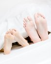Close up of feet of the couple lying in bed Lizenzfreie Stockfotos