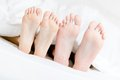 Close up of feet of the couple lying in bed-room Royalty Free Stock Image