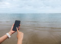 Close up of female hand holding smart mobile phone with blank screen on the beach with clear sky beach sand and wave used as temp Royalty Free Stock Image