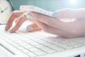 Close up of female hand using mobile phone and laptop computer, Working woman and Online shopping Royalty Free Stock Photo