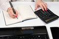 Close-up of female hands with calculator, fountain pen and noteb Royalty Free Stock Photo