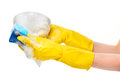 Close up of female hands in yellow protective rubber gloves washing white bowl with blue cleaning sponge Royalty Free Stock Photo