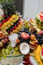 Close up of festive table different fresh fruits with pineapple, coconut, grapes, berries, watermelon, apples, pomegranate. Royalty Free Stock Photo