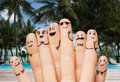 Close up of fingers with smiley faces on beach Royalty Free Stock Photo