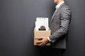 Close up of fired man employee hiding behind box with personal items on grey background Royalty Free Stock Photo