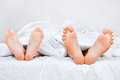 Close up of four feet in a bed Royalty Free Stock Photography
