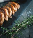 Close-up of fresh rosemary with roasted pork chops in background Royalty Free Stock Photo