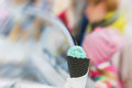 Close-up of fruit Ice-cream green color in Black waffle cone, background with sweet dessert. Real scene in store Royalty Free Stock Photo