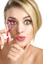 Close up of a funny beautiful girl using eyelash curler on white Stock Photos