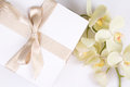 Close up of gift box with ribbon and orchid flower Royalty Free Stock Photo