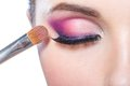 Close up of girl applying bright makeup brush pink on eye pretty isolated on white Stock Photography