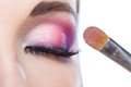 Close up of girl with closed eye applying makeup bright pink brush isolated on white Royalty Free Stock Photography