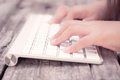 Close up girl hand typing keyboard on wood table use filtered images Stock Photos