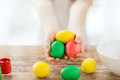 Close up of girl holding colored eggs easter holiday and child concept little with colors and bowl on the table Stock Photo