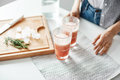 Close up of girl`s hands glasses with grapefruit detox diet smoothie rosemary and ice pieces on wooden desk.