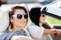 Close up of girls in sunglasses in the convertible car wearing little holiday trip friends Stock Image