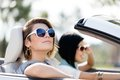 Close up of girls in sunglasses in the white car Stock Photos