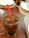 Close-up glass of cola with ice cubes and straw Royalty Free Stock Photo