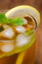 Close up of glass iced tea with lemon and mint selective focus on a wooden background Stock Images