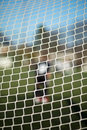 Close up of goal net soccer with blurred goalie in the background Royalty Free Stock Photos