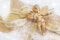 Close up of golden present box with angel playing violin for christmas on snowy background Royalty Free Stock Photo