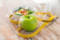 Close up of green apple and measuring tape Royalty Free Stock Photo