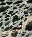 Close up of grey eroded rocks on a beach, covered with sand. Royalty Free Stock Photo