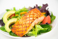 Close up grilled salmon salad mixed greens tomatoes avocado shallow depth field Royalty Free Stock Photography
