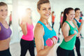 Close-up of group of young women doing exercise with dumbbells Royalty Free Stock Photo