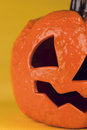 Close up of a halloween pumpkin on yellow background Stock Photo