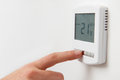 Close up of hand adjusting digital central heating thermostat co Stock Image