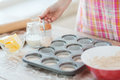 Close up of hand filling muffins molds with dough cooking and home concept Stock Photo