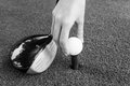 Close-up Hand holding golf ball and a golf wood on a driving ran Royalty Free Stock Photo
