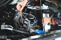Close up hands checking lube oil level of car engine from deep-stick for service and maintenance concept