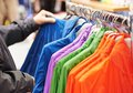 Close up hands choosing clothing of man t shirt and parka during shopping at store Royalty Free Stock Image