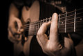 Close up hands on the strings of a guitar Royalty Free Stock Photo