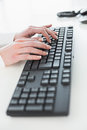 Close up of hands using computer keyboard in a bright office Stock Photos