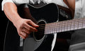 Close-up of hands of a young man playing guitar on a black background. Musical instrument, art concept. Royalty Free Stock Photo