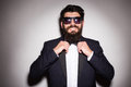 Close-up of handsome young man wearing sunglasses adjusting his bow tie and looking at camera Royalty Free Stock Photo